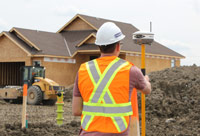 Surveyor taking GPS measurements in front of a home construction site
