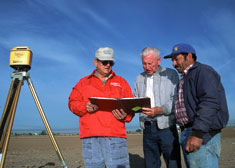 Three men consulting a workplan in the field